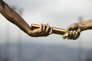 two hands passing a baton