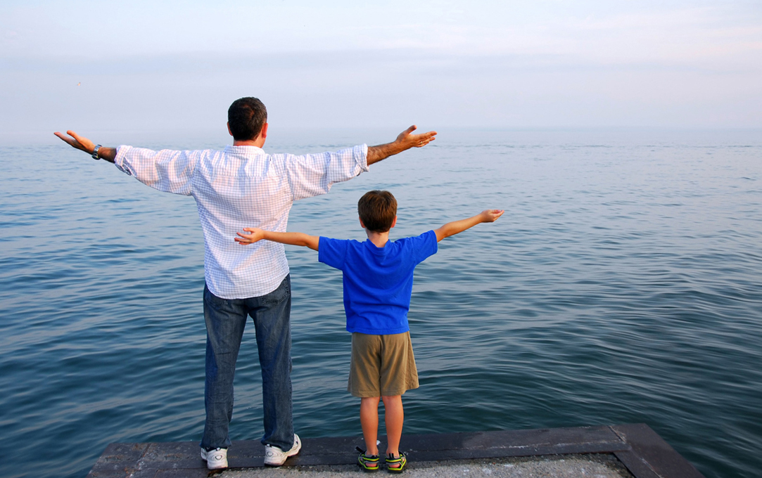 Man and Son Standing on the Edge of a Sea